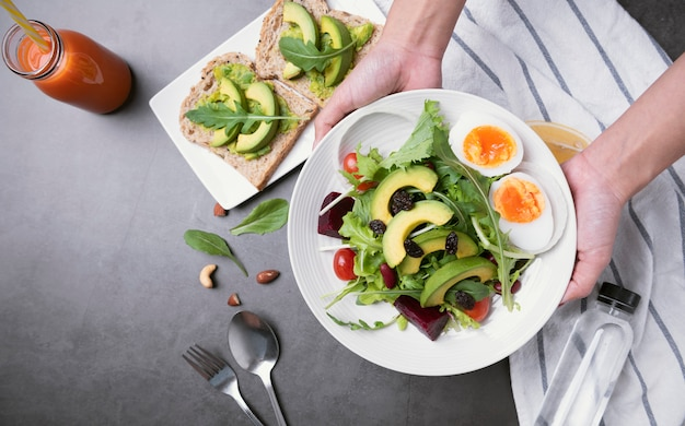 Frischer gesunder gemüsesalat mit ei, tomate, avocado, spinat, kopfsalat in der platte auf tabellenhintergrund.