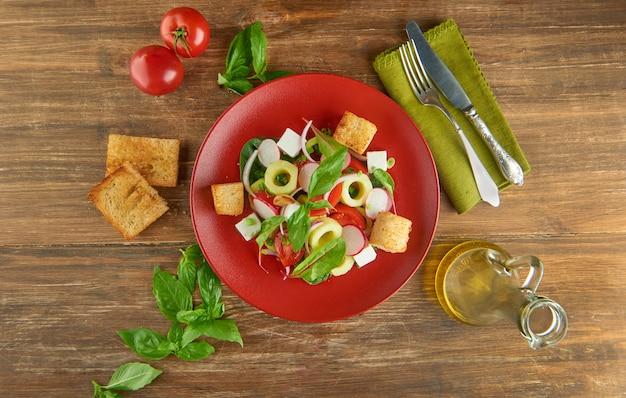 Frischer gesunder salat auf rotem teller und basilikumblättern auf holztisch. sicht von oben