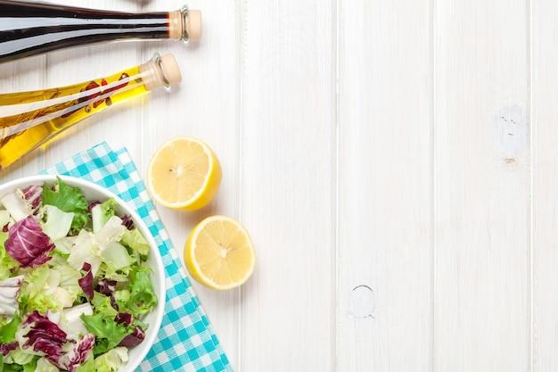 Frischer gesunder salat und gewürze über weißem holztisch. ansicht von oben mit kopienraum