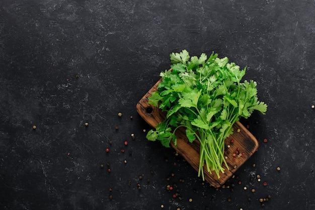 Frischer gewürzkoriander auf einem holzbrett mit paprika auf schwarzem hintergrund mit kopierraum.