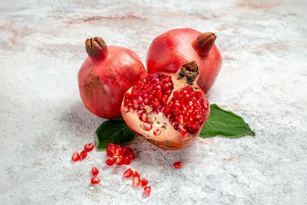 Frischer granatapfel der vorderansicht auf weißem raum