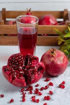 Frischer granatapfel in scheiben oder ganz mit glas saft auf grauer wand.