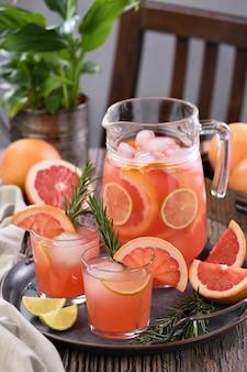 Frischer grapefruitcocktail. frischer sommercocktail mit grapefruit, limette, rosmarinzweig und eiswürfeln.