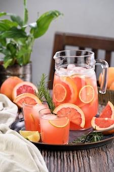 Frischer grapefruitcocktail frischer sommercocktail mit grapefruit-limettenzweig rosmarin