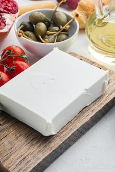 Frischer griechischer feta-käse eingestellt, auf weißem tisch