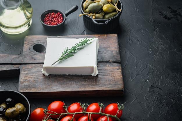 Frischer griechischer feta-käse gesetzt, auf schwarzem tisch