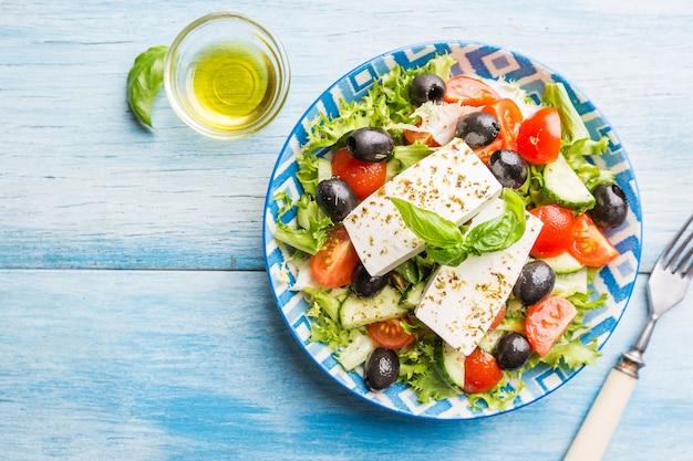Frischer griechischer salat aus gurke, tomate, paprika, roten zwiebeln, feta-käse und oliven mit olivenöl