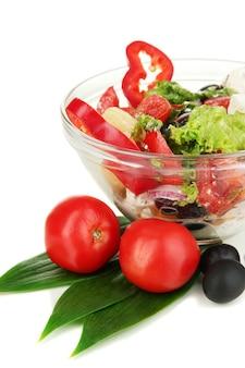 Frischer griechischer salat in der glasschale lokalisiert auf weiß