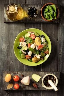 Frischer griechischer salat in teller und zutaten auf holztisch