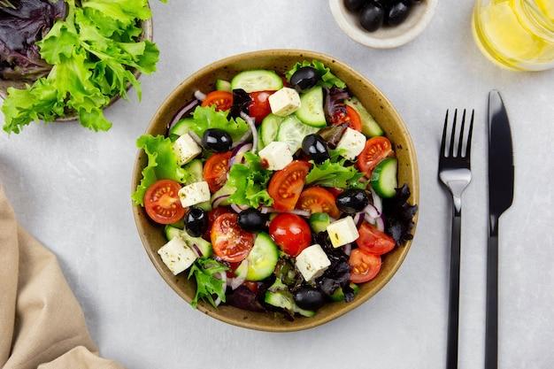 Frischer griechischer salat mit kirschtomate, gurke, salat, schwarzer olive, feta-käse und olivenöl auf hellgrauer oberfläche