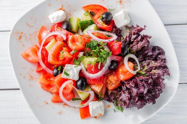 Frischer griechischer salat mit zwiebel auf weißer platte und holztisch