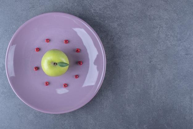 Frischer grüner apfel auf lila platte.