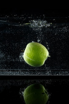 Frischer grüner apfel, der im wasser auf schwarzem hintergrund spritzt