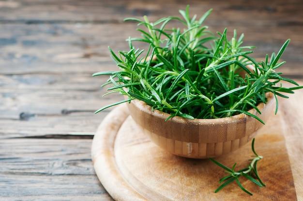 Frischer grüner aromatischer rosmarin auf dem holztisch