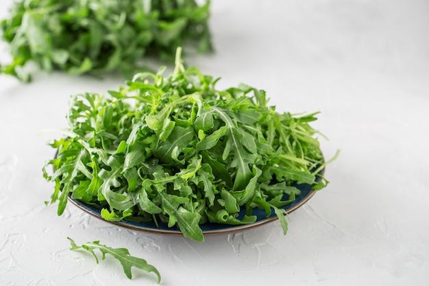 Frischer grüner arugula in der schüssel auf tabelle. rucola für salat