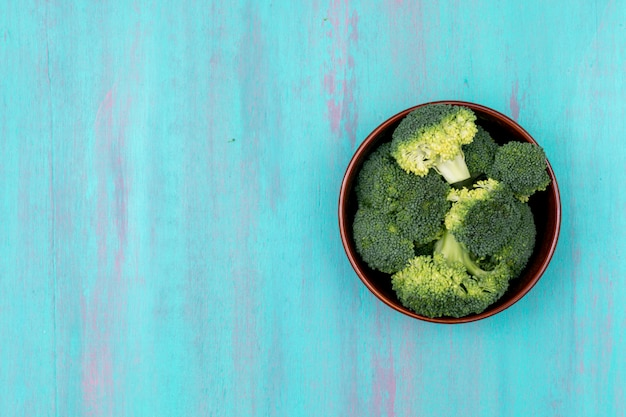Frischer grüner brokkoli der draufsicht auf platte auf blauer holzoberfläche