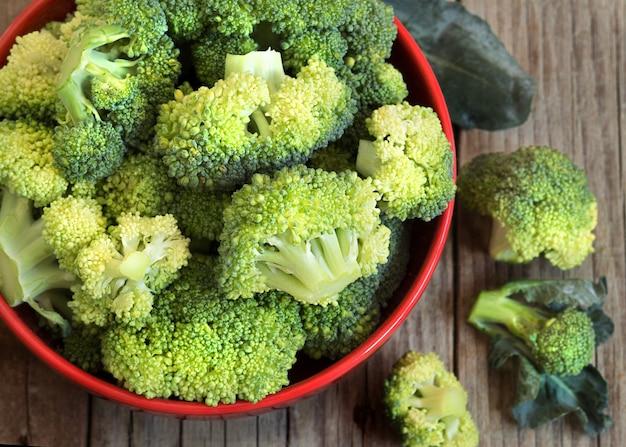 Frischer grüner brokkoli in einer roten schüssel auf holztisch schließen oben