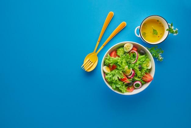 Frischer grüner gemüsesalat mit salat, tomaten und gurke in weißer schüssel