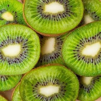 Frischer grüner kiwifruchthintergrund. flache lage, draufsicht, lebensmittelkonzept. lebensmittelrahmen mit kopierraum für ihren text. banner. grüne kiwi kreist textur ein