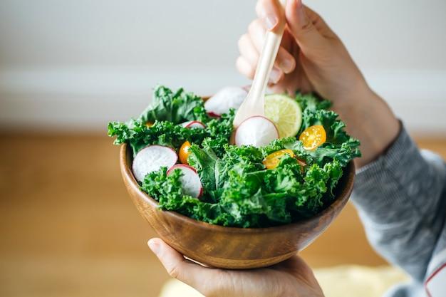 Frischer grüner salat in einer holzschale.