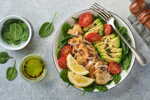 Frischer grüner salat mit gegrilltem hühnerfilet, spinat, tomaten, avocado, zitrone und schwarzem sesam mit olivenöl in weißer schüssel auf hellem schieferhintergrund. diät-konzept. kopienraum der draufsicht