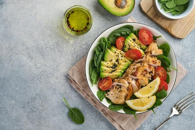 Frischer grüner salat mit gegrilltem hühnerfilet, spinat, tomaten, avocado, zitrone und schwarzem sesam, olivenöl in weißer schüssel auf hellem schieferhintergrund. ernährung-diät-konzept. ansicht von oben. platz kopieren