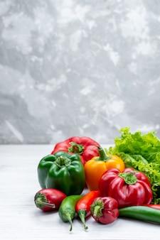 Frischer grüner salat zusammen mit farbigen paprika und würzigen paprika auf hellem schreibtisch