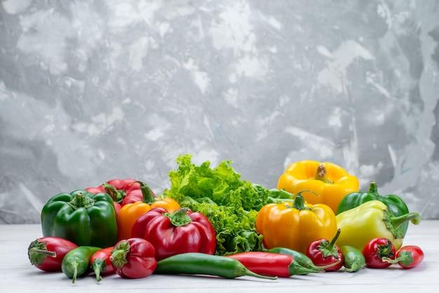 Frischer grüner salat zusammen mit farbigen paprika und würzigen paprika zusammensetzung auf hellem schreibtisch
