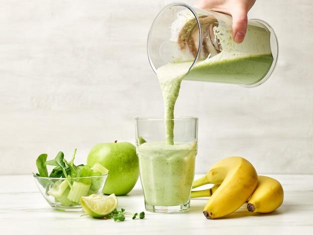 Frischer grüner smoothie, der in glas gießt, bereit für gesundes frühstück