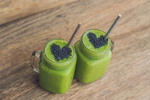 Frischer grüner smoothie mit banane und spinat mit herz aus sesam