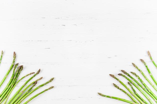Frischer grüner spargel auf weißer holzoberfläche
