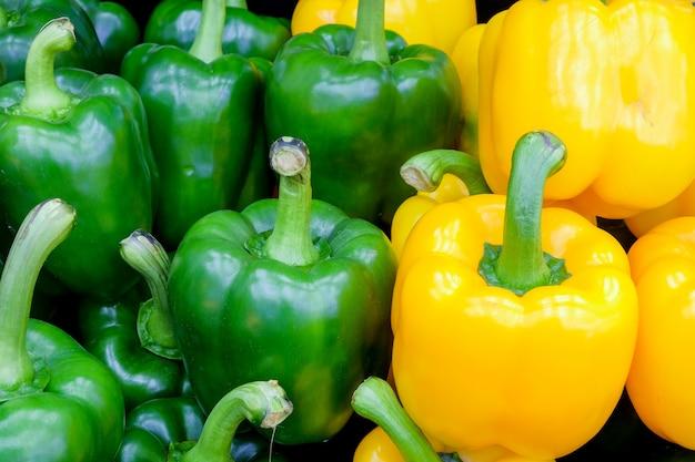 Frischer grüner und gelber grüner pfeffer der nahaufnahme (gemüsepaprika oder spanischer pfeffer) auf frischmarkt