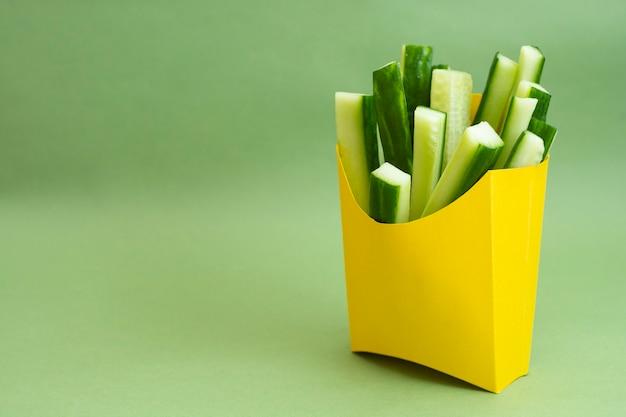 Frischer gurkensticksnack in gelber pappschachtel auf grünem hintergrund