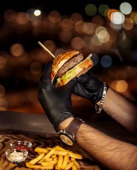 Frischer hamburger in schwarzen handschuhen