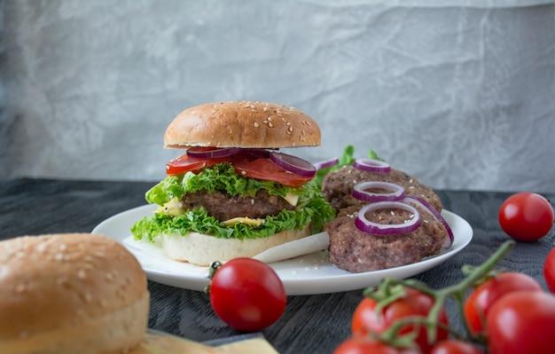 Frischer hausgemachter burger. frisches gemüse, kräuter und rindfleischkoteletts zum kochen eines burgers