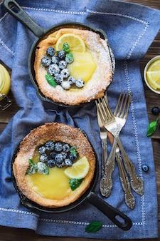 Frischer hausgemachter dutch baby pancake mit lemon curd und blaubeeren in eisenpfannen