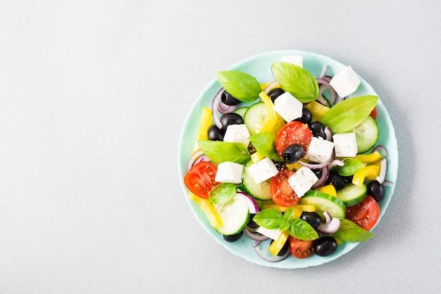 Frischer hausgemachter griechischer salat mit basilikumblättern auf einem teller auf dem tisch