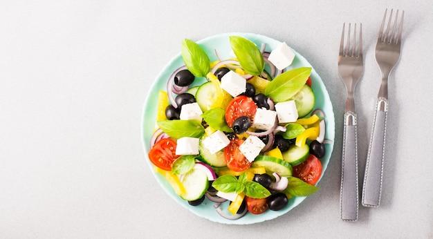 Frischer hausgemachter griechischer salat mit basilikumblättern auf einem teller und gabeln auf dem tisch