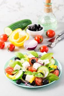 Frischer hausgemachter griechischer salat mit basilikumblättern auf einem teller und zutaten zum kochen auf dem tisch