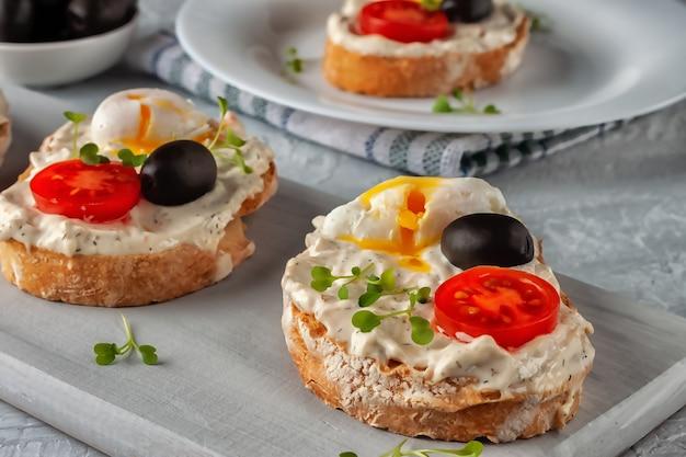 Frischer hausgemachter knuspriger brottoast mit tomaten, pochiertem ei und oliven. ein schneller snack aus gutem essen