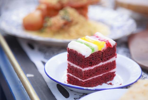 Frischer hausgemachter köstlicher roter samtkuchen mit bunter schlagsahne