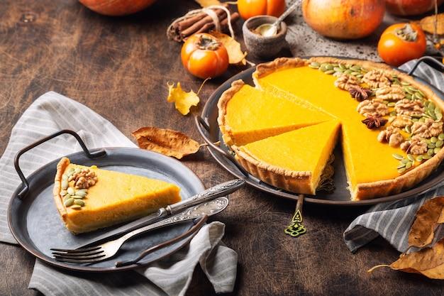 Frischer hausgemachter kürbiskuchen zum erntedankfest, dekoriert mit walnüssen und samen. am vintage-tablett auf rustikalem sperrholz in stücke geschnitten.