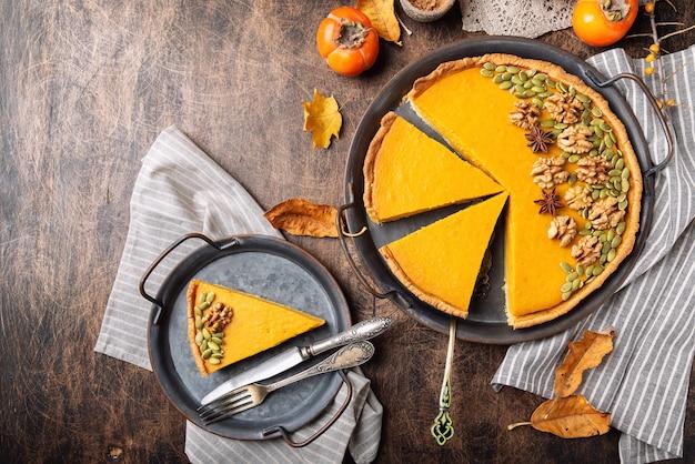 Frischer hausgemachter kürbiskuchen zum erntedankfest, dekoriert mit walnüssen und samen. auf vintage-tablett auf rustikalem sperrholz in stücke geschnitten. draufsicht