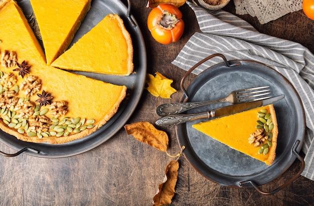 Frischer hausgemachter kürbiskuchen zum erntedankfest, dekoriert mit walnüssen und samen