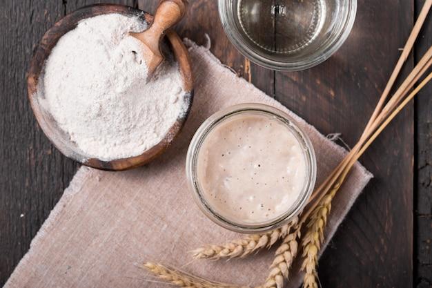Frischer hausgemachter sauerteig-starter, eine fermentierte mischung aus wasser und mehl, die als sauerteig zum brotbacken auf einem holztisch verwendet werden kann