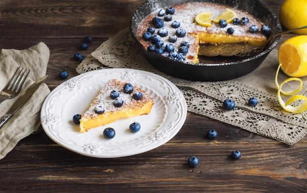 Frischer hausgemachter zitronenkuchen mit blaubeeren in eisenpfanne auf rustikaler holzoberfläche. selektiver fokus.