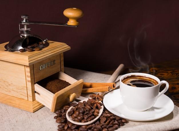 Frischer heißer kaffee im weißen becher neben der mühle neben dem stapel bohnen und zimtstangen auf dem tisch, der mit natürlich getönter leinwand bedeckt ist