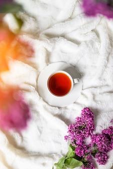 Frischer heißer schwarzer tee in einer schönen porzellantasse mit einem lila blumenstrauß, flach gelegt