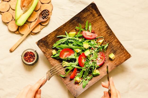 Frischer hellgrüner salat mit avocado und tomaten in einer hölzernen platte.