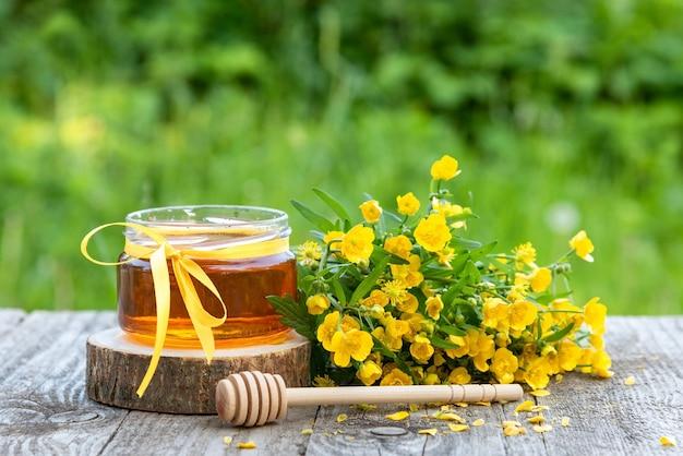 Frischer honig im glas und gelbe blumen.